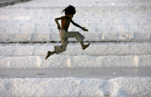 A worker's son plays in a salt pan near Bhavnagar, in the western Indian state of Gujarat March 5, 2009. REUTERS/Arko Datta (INDIA) - RTXCEC4